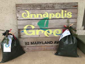 bags of compost with an annapolis green sign