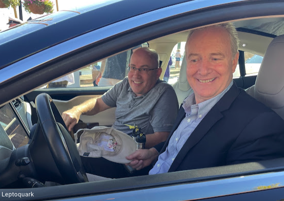 two men smiling in an electric vehicle